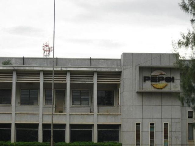 This is the former Pepsi Cola bottling plant which was located in Battambang, Cambodia. The vast warehouse still contains the original bottling machinery from the 1960's plus about 10,000 bottles of Pepsi, Miranda, Singha Soda, Teem… In fact, the factory was abruptly shut down when the Khmer Rouge took over Battambang in 1975. But there is always one old man though who takes care of the lawn and trims the hedges…