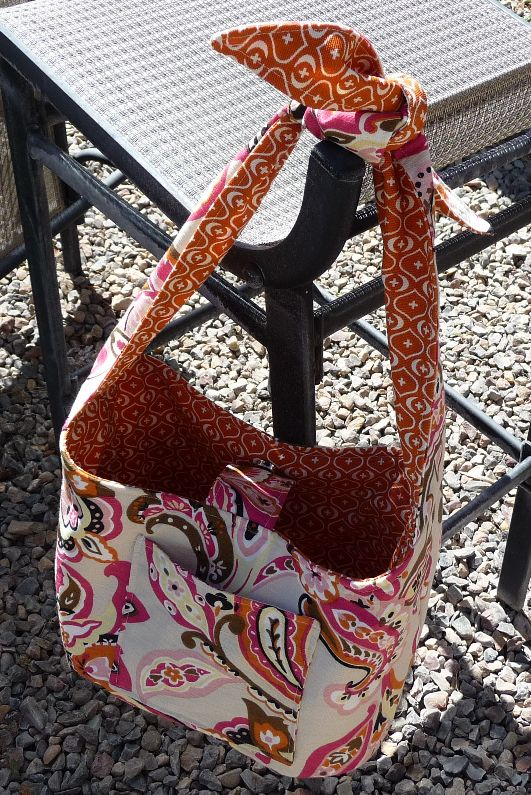 This cute handbag has a strap that's actually just two separate straps tied together at the top. It's also fully reversible. No matter which way you have it, it will have a pocket inside and a po...