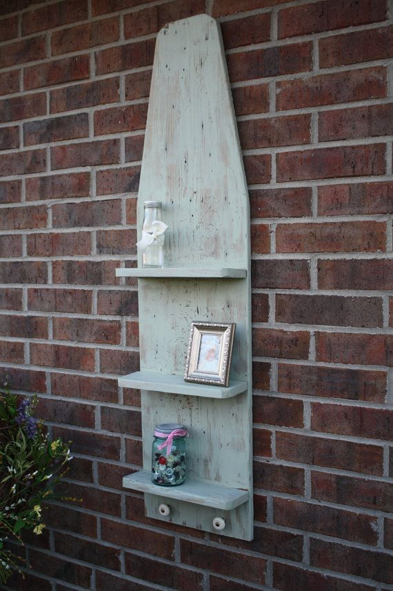 Repurposed wooden ironing board with added shelves and knobs.