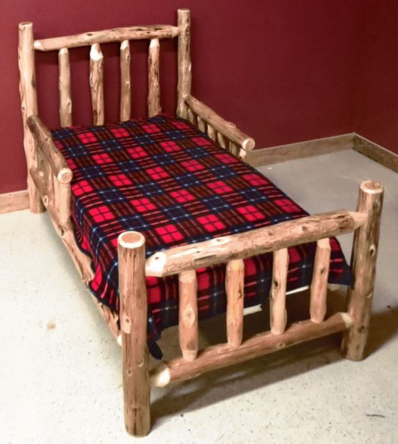 This cedar log toddler bed is made from northern white cedar and features side rails for safety. The bed works with a standard crib mattress