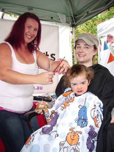 Jasper, 2, of Indooroopilly gets a professional kiddy cut courtesy of Renee Houston at the Mummy Tree Markets
