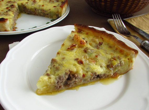 Meat and potato pie | Food From Portugal. A delicious pie, with excellent presentation, stuffed with meat seasoned with pepper, garlics and salt,  confectioned with tomato, onion and olive oil, wrapped in fried potatoes, covered with a béchamel mixture. http://www.foodfromportugal.com/recipe/meat-potato-pie/