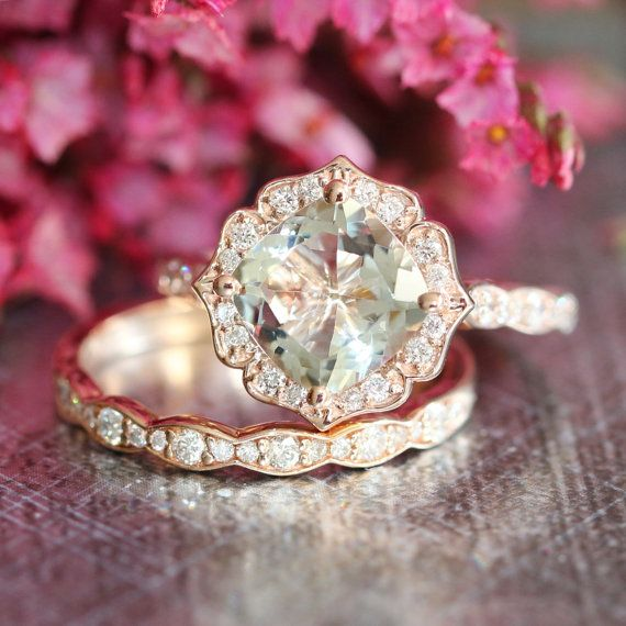This vintage inspired bridal wedding ring set showcases a floral engagement ring with 8x8mm cushion cut natural light green amethyst set in a solid
