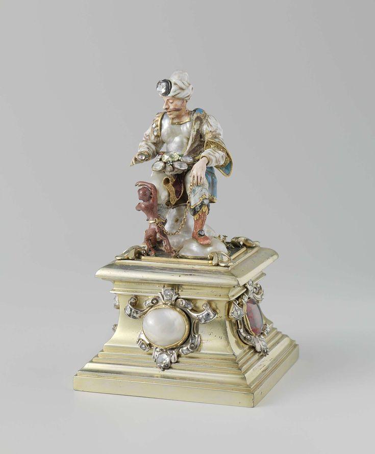 Anonymous | Armeense koopman met aap, Anonymous, c. 1700 - c. 1725 | Beeld van goud, barok-parels en edelstenen, voorstellende een Armeen gezeten op een parel als stoel. Een bruin aapje houdt hem een diamant voor. Het tafereeltje staat op een voetstuk versierd met edelstenen.