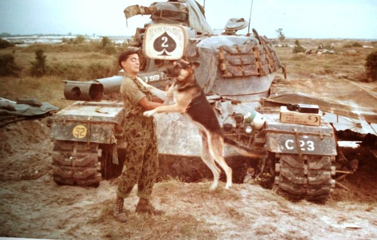 Marine Jimmy Logan playing a dog in front of a M48 Patton tank.