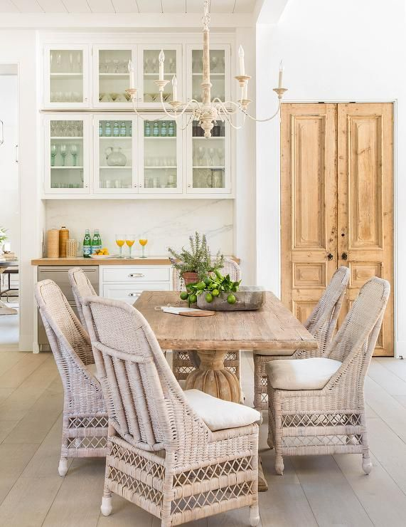 Gorgeous kitchen features a French chandelier illuminates a reclaimed wood dining table lined with wicker dining chairs.