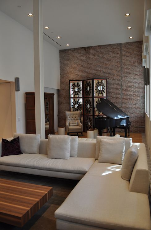 Chic loft liv ing room design with exposed brick wall, baby grand piano,  tufted chair, mirrored folding screen, ivory linen sectional sofa ...