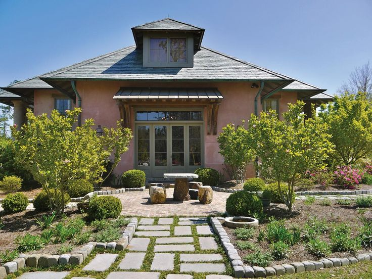 A Southwestern style home's exterior features a sunny stone patio and walkway. Stone pavers create a border for a planting bed and a stone table and stools provide an outdoor dining space.