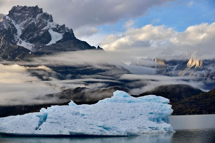 Katsu Tanaka photo of an iceberg on the water in front of mountains and blue sky with clouds and fog, shot in Patagonia.