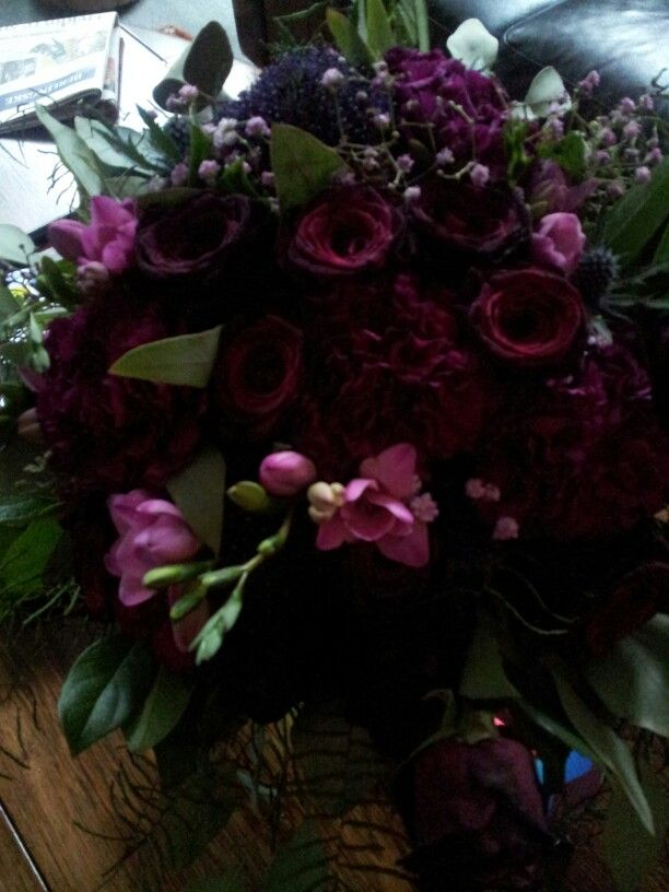 My beautiful bouquet,  with deep berry roses, purple carnations, pink freesia, purple pompoms and pink baby's breath.