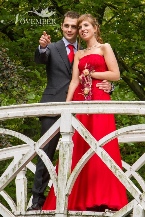 Een rode strapless trouwjurk in lichte a-lijn overtrokken met Italiaans kant. Het bovenstuk van de trouwjurk heeft een strapless square halsuitsnijding, en is afgewerkt met een vetersluiting. De bruidsjurk is verder afgewerkt met een sleep.  Klik op de foto om naar de website te gaan en meerdere foto's te bekijken.