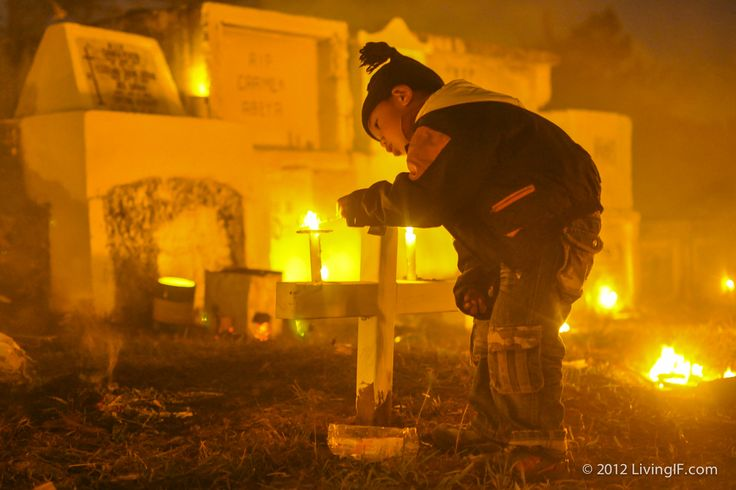 Child lighting a candle on a family grave for All Souls Day; Sagada, Philippines.
