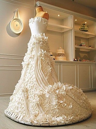 Wedding Dress Cake: This stunning wedding dress cake is truly food as art.  It is so intricately decorated that it almost appears wearable.  The bodice is designed simply with a few details while the skirt is covered in swirls, ridges, and calla lilies.  This wedding dress cake almost looks good enough to wear.