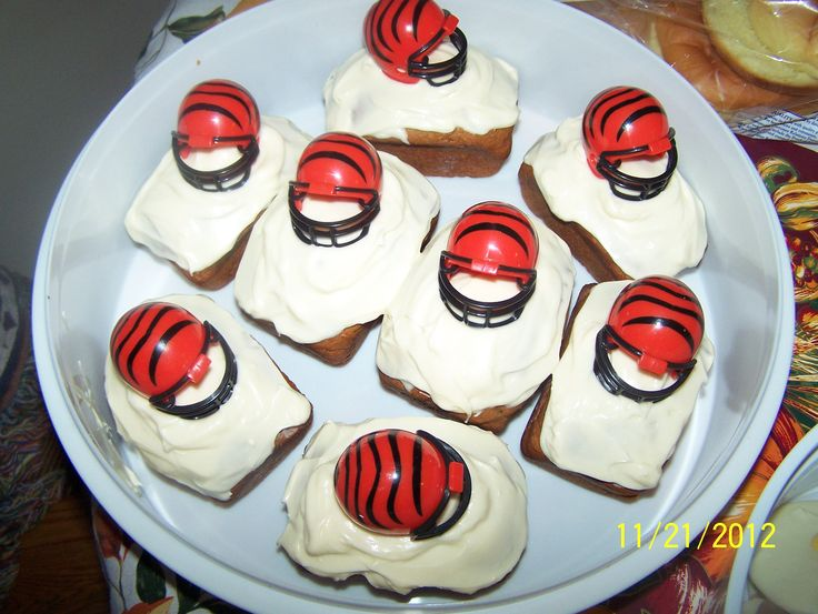 pumpkin cakes with cream cheese icing, decorated with a bengal helmet