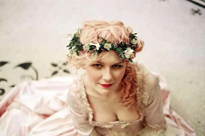 renaissance hairstyles, kirsten dunst, dressed as marie antoinette, with pale pink, frilly and shiny dress, pink curly hair in side ponytail, and green wreath with white flowers