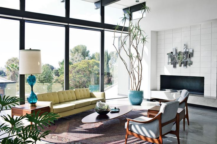 A Nelson sofa sits on a handmade Persian Mahi rug in the living room with floor-to-ceiling windows