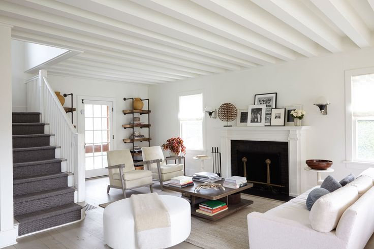 Elegant neutral living room with white sofa and accents chairs, dark fireplace and white painted beams on the ceiling.