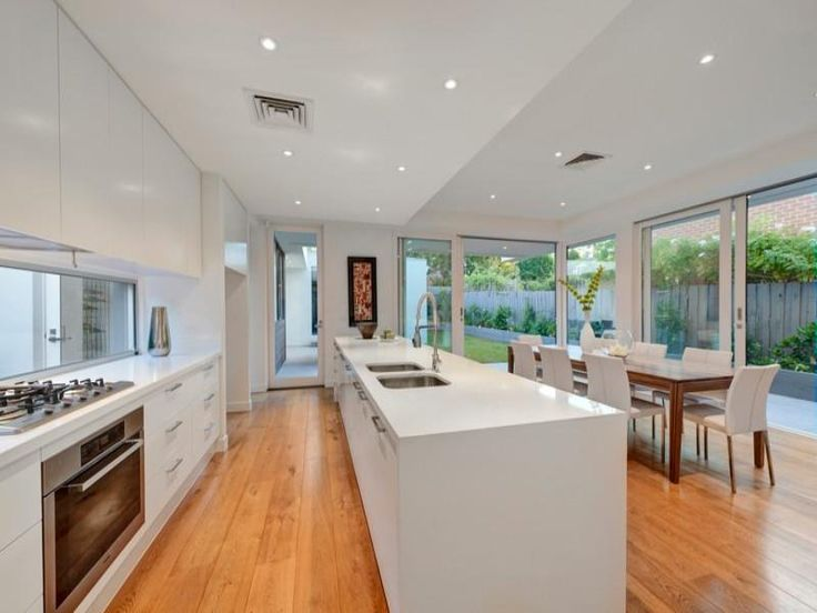 White kitchen, window splashback, wooden floor,