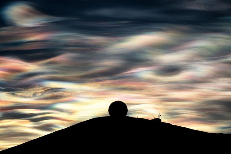 Rare nacreous clouds over the NASA Radome at McMurdo Station on Ross Island in Antarctica. Photograph by Deven Stross.