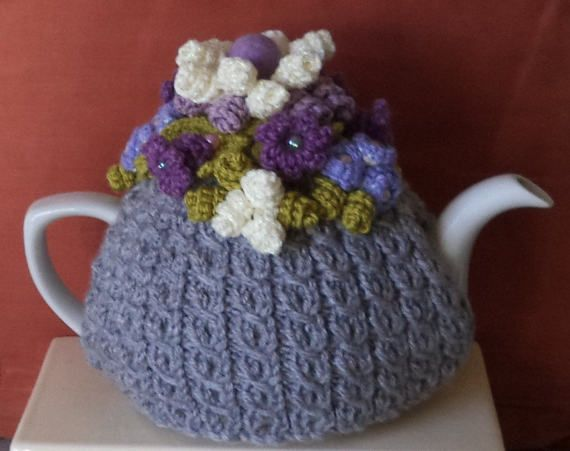 knitted to my own pattern and design, this cosy is in a double strand of double knitting in misty grey in a lovely mock cable pattern with stocking top...  soft, thick and warm to keep tea nice and hot, it measures 16 inches by 7.5 inches and is a lovely fit for a standard, round 6 cup tea pot....  the decoration includes: a large double curlicue 16 petal flower, made to my own design, in lavender milk cotton yarn and sparkly cream yarn..the blossom has a lovely lavender wool felt ball in…