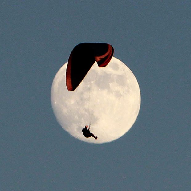 A paraglider sails past the moon above the hills in Tehachapi, California