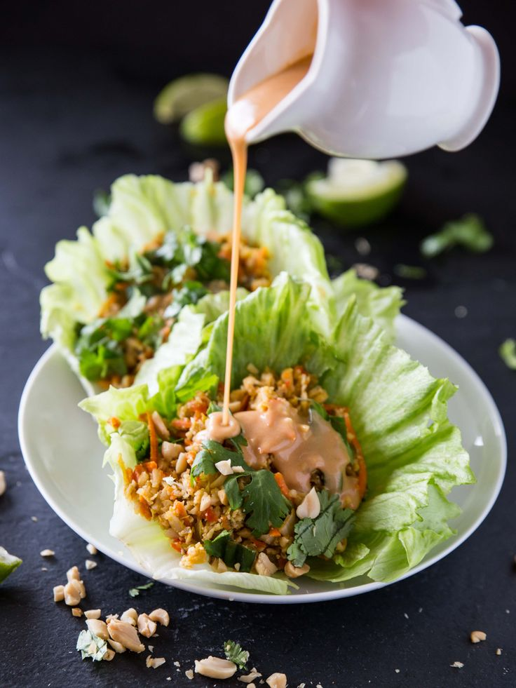 Veggie-packed lettuce wrapped made with cauliflower rice, seasoned with soy sauce and lime juice, and served with a spicy sriracha peanut sauce.