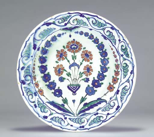 AN IZNIK POTTERY DISH  OTTOMAN TURKEY, CIRCA 1640  With sloping rim on short foot, the white interior painted in cobalt-blue, green and bole-red, with a central bouquet of red carnations flanked by blue and red floral sprays issuing from the centre with saz leaves, the border painted with scolling blue and green motifs, the base with blue alternating trefoils and simple flowerheads,   11in. (27.8cm.) diam.