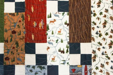 River Journey is a great gift for that nature lover in your life. Fishing and kayaking are depicted in the fabrics. A navy and cream check pattern accents the quilt as well.