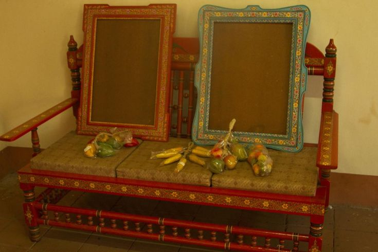 An old wooden sofa and frames painted in Ganjifa style.An old wooden chair painted with floral patterns.A game known as chaturanga painted in Ganjifa style. An old wooden sofa and frames painted in Ganjifa style.