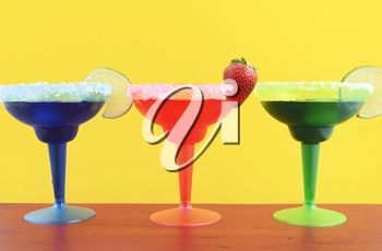 Happy Cinco de Mayo colorful party theme with bright color margarita drinks on red wood table and yellow background.