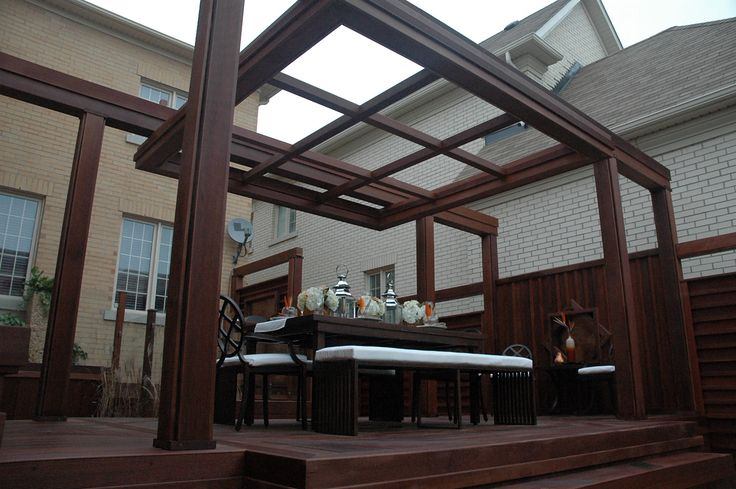 """Massaranduba hardwood deck with glass railing and pergola, featured in """"Decked Out"""" epsode """"The Big Table Deck"""".  Deck design by Paul Lafrance Design."""