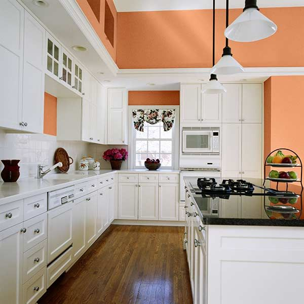 An all-white kitchen is warmed up by a summery peach hue on the walls. | Slightly Bittersweet B21-2; @dutchboypaint