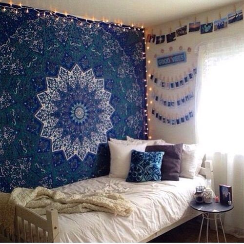 cool pictures above bed with tapestry. bed in corner of room near window with small n...