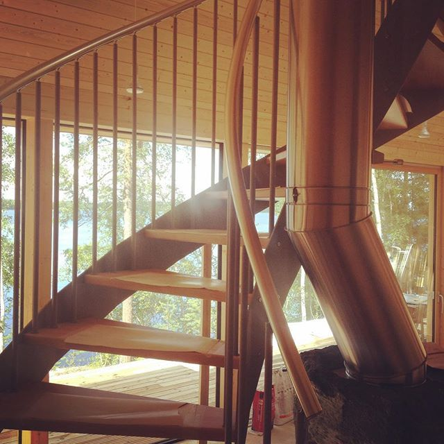 Staircase at Pyramid House. The helicoidal suspended staircase wraps around the rough soapstone fireplace and allows the stainless steel chimney to run through the middle
