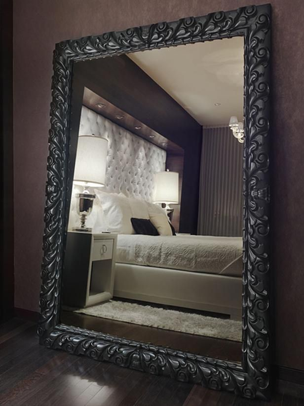 Oversized Mahogany Mirror On Wood Floor Of Bedroom Reflects White Bed