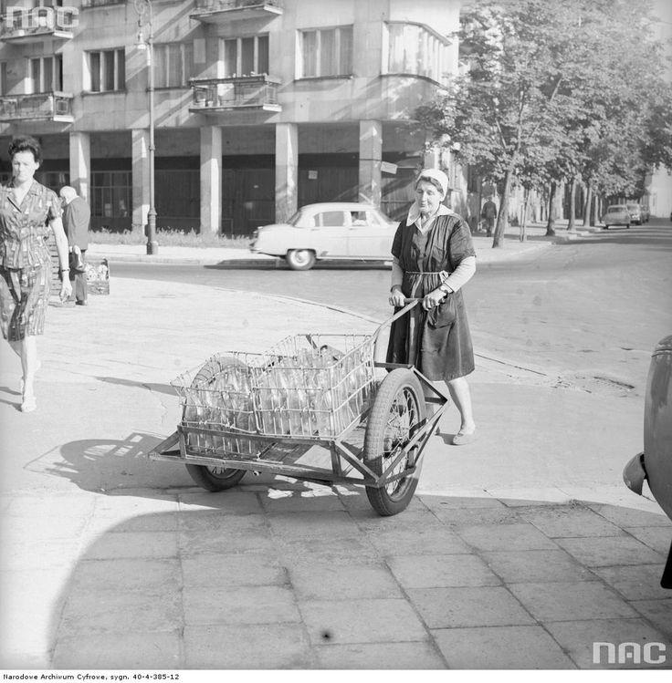 Kobieta prowadzi wózek ze skrzynkami butelek po mleku na skrzyżowaniu ul. Chocimskiej i Skolimowskiej. W tle kamienica przy ul. Skolimowskiej 4.