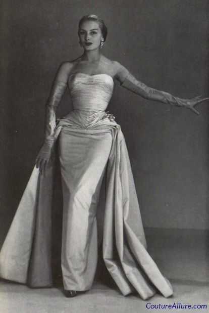 White satin is molded to fit the body with tucks galore on the bodice.  And look how the yards of fabric used for the overskirt fall gracefully from the folds at the hips