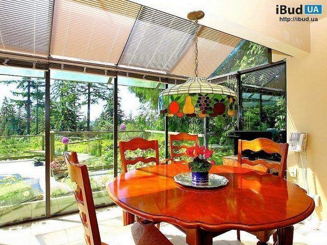 На фотографии показан дизайн столовой со стеклянными стенами. Они наполняют комнату дневным светом, делают интерьер светлее и уютнее. В столовой разместили круглый стол и стулья, они сделаны из дер...