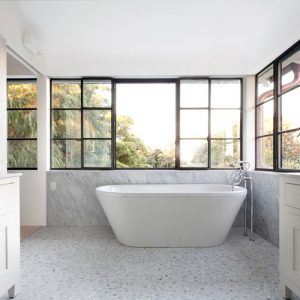 A spacious bathroom with freestanding tub, gray marble walls and gray pebble tiles. / Photo by Decus Interiors