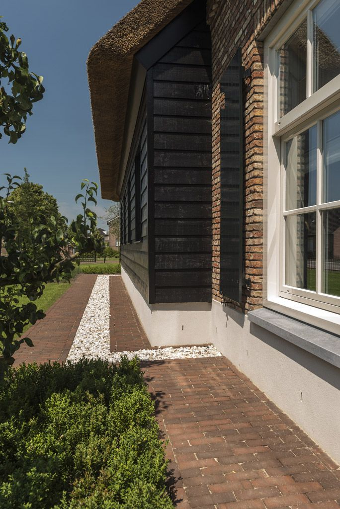 Pad van Bylandt gebakken klinkers met witte kiezel naast een boerderij met rieten dak