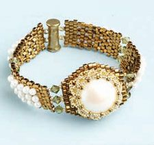 Wow, this is beautiful... looks like a watch! A beautiful pearl cabochon becomes the focal point of this spectacular bracelet. Pearlescent drops and bronze cubes create elegant peyote-stitch straps that complement a pearl cabochon encased in a lacy netted bezel.