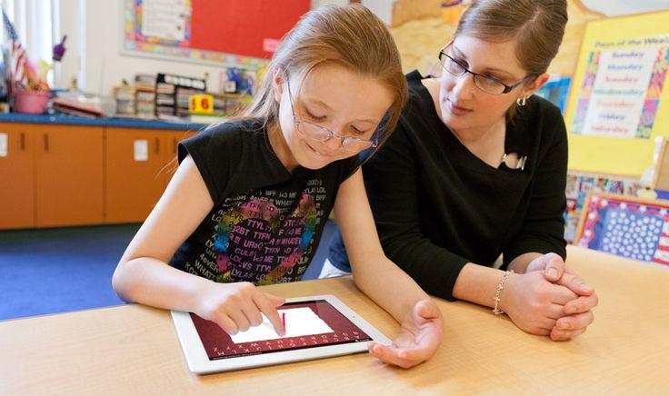 Teacher sitting with student using an iPad.