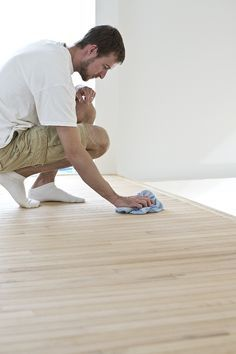Wiping dust from a hardwood floor after using a floor sander