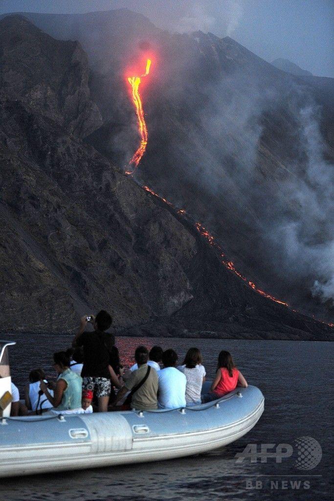 イタリア南部のシチリア(Sicily)島沖にあるストロンボリ(Stromboli)島で、ストロンボリ火山から噴出した溶岩が海に流れ込む様子をボートに乗って見学する観光客たち(2014年8月9日撮影)。(c)AFP/GIOVANNI ISOLINO