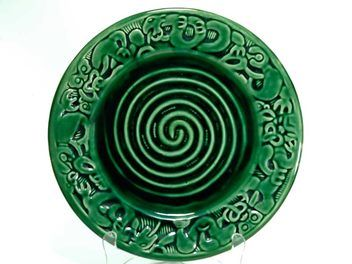 CROWN LYNN  MADE IN NEW ZEALAND    WHARETANA WARE    NUMBER 1021    WHARETANA SPIRAL WALL PLATE  Plain dark green glaze. Sold for $1507.00 April 2016