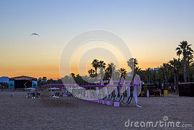 Scenic colorful sunset at the sea coast with beach umbrellas, Costa Darado, Spain