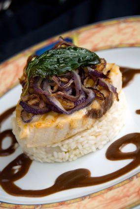 Un rico filete de pescado con champiñones sobre una cama de arroz.