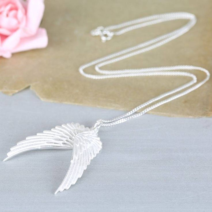 Fly straight to the top of the new season cool wearing this sensational sterling silver angel wing necklace from Kitten Jewellery.Fashion will come and go, but killer styles such as angel wings and feathers will always stand the test of time, and this elegant necklace will take your style potential sky high. With two angel wings hanging from a shiny curb chain and a brushed metal finish on the highly detailed feather front of the wings. Team this stunning necklace with glitzy evening…