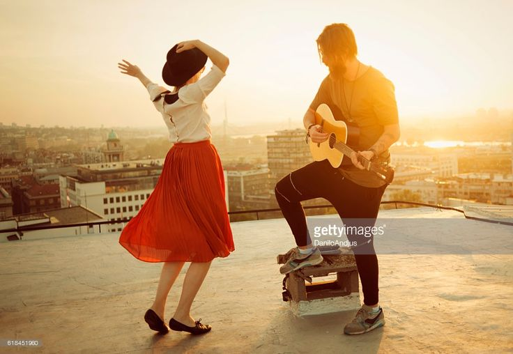 couple dancing on the roof playing the guitar on sunset
