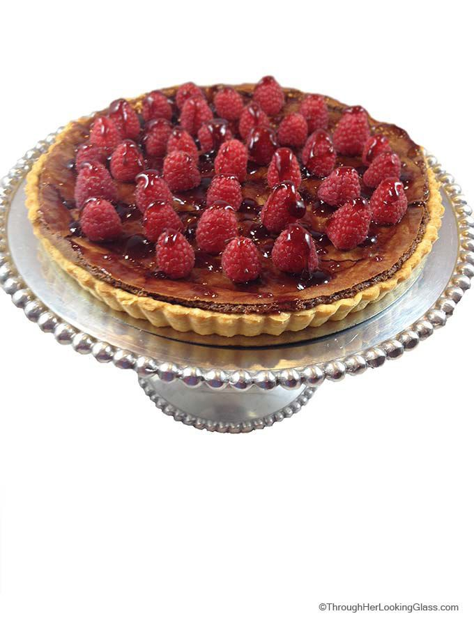 Decadent Chocolate Raspberry Tart. A stunning, elegant dessert perfect for any special occasion. Surprisingly easy to make. The perfect ending to a wonderful meal. @driscollsberry #raspberrydessert